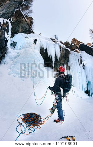 A climber belays the leader during a ice climbing. Lillaz Icefall, Cogne (Val d'Aosta) - Italy.