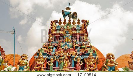 Decorated temple entrance gopuram or tower captured against cloudy sky background