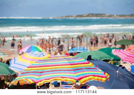 Beach Scene With Colorful Umbrellas And People On The Beach