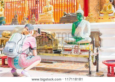 Chinese Tourist Using A Smartphone To Take A Photo Of A  Buddha Statue