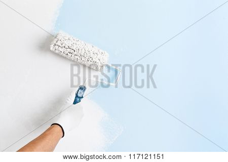 Close up of painter hand in white glove painting a wall with paint roller; copy space poster