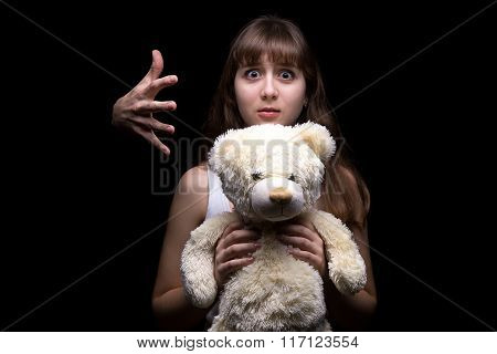 Scared teenage girl with toy