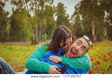 Young couple sitting on the grass in a field of red poppies. The girl kiss the guy while he has a si