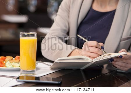 Cheerful young businesswoman has a lunch in cafe