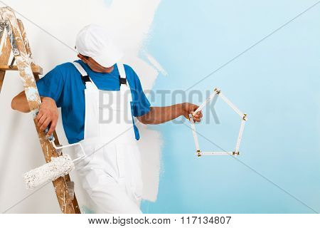 Painter With Paintroller Showing A Yardstick House