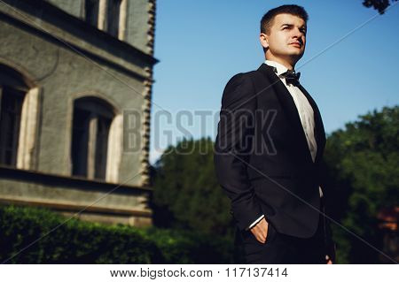 Handsome Wealthy Confident Groom Near Old Mansion Background At Sunset