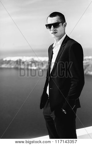 Handsome Strong Confident Groom Posing On Roof With Sea And Mountains Background B&w