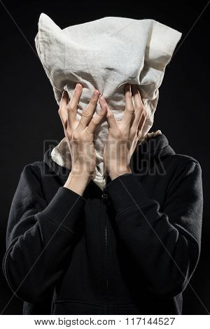 Anonymous figure covered in a bag with hands over face