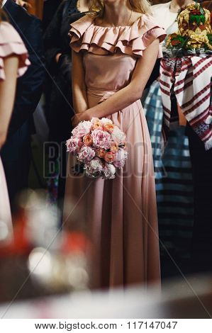 Beautiful Elegant Bridesmaid In Pink Dress Holding A Rose Bouquet In Church At Wedding Ceremony