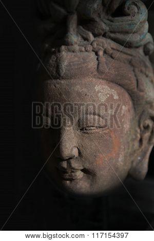 Buddha head statue in shadow