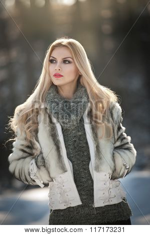 Attractive young Caucasian woman with short fur jacket in winter park. Beautiful blonde girl