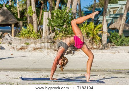 outdoor portrait of strong woman in sportwear doing workout stretching on tropical beach at sunset. Female sporty muscular body. Dawn bright sunny light.