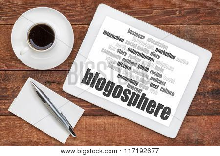 blogosphere word cloud on a digital tablet with a cup of coffee and note pad - blogging concept