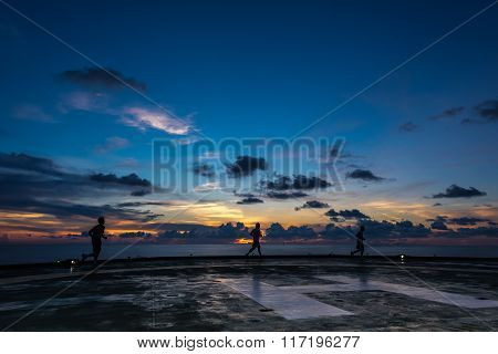 Three men running on oil rig helipad in Gulf of Thailand in sunset time with helipad light on