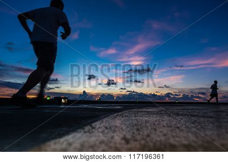 Two men running on oil rig helipad in Gulf of Thailand in sunset time with helipad light on ** Note: Visible grain at 100%, best at smaller sizes