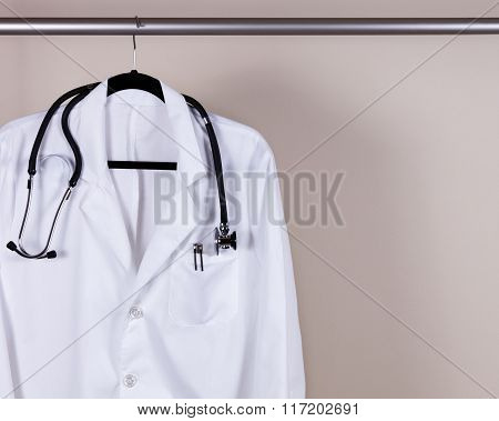 Medical White Consultation Coat With Stethoscope And Pens On Hanger