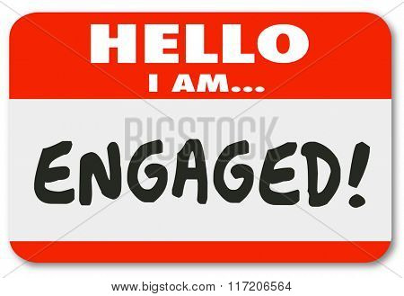 Hello I Am Engaged words on a nametag sticker to illustrate your involvement, interest or paying attention or your status as a fiancee for marriage following a wedding proposal poster