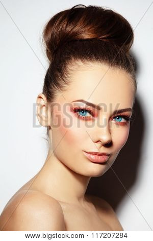Young beautiful woman with sunny fresh make-up and hair bun