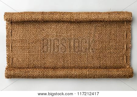 Frame Of Burlap With Curled Edges In The Form Of A Scroll, Lies On A White Background