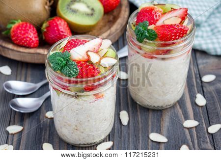 Overnight Oatmeal With Fresh Strawberry And Kiwi, Garnished With Sliced Almond In  Glass Jar