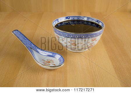 Molasses in porcelain bowl with porcelain spoon.