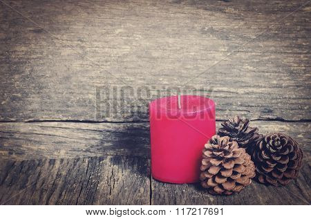 Red Christmas candle and three pine cones on wooden table with vintage and vignette tone
