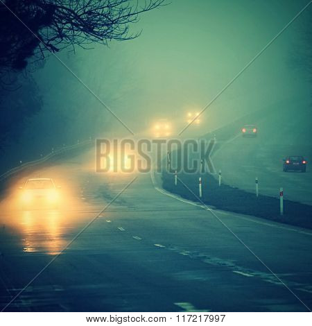 Cars in the fog. Bad winter weather and dangerous automobile traffic on the road.