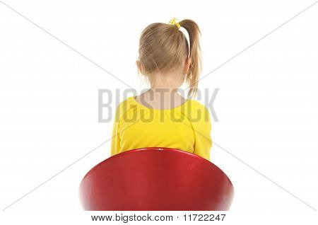 Girl sits on chair back to camera