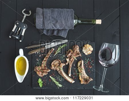 Grilled lamb chops. Rack of Lamb with garlic, rosemary, spices on slate tray, wine glass, oil in a s