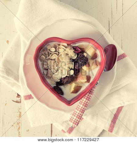 Musli in heart shaped bowl, white wood background
