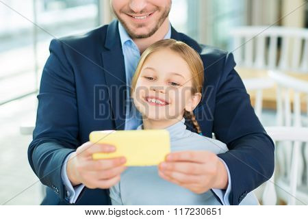 Young adoring dad taking picture of cute daughter.