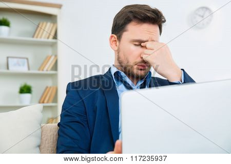 Handsome young man looks overwhelmed with work