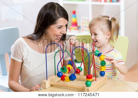 child and mother playing together with educational toy in nursery