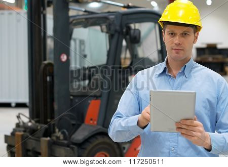 Warehouseman In Hard Hat With Tablet Pc At Warehouse.