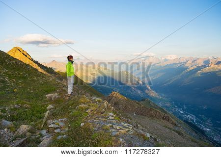 Woman Watching Sunrise Over The Alps In Valle D'aosta, Italy