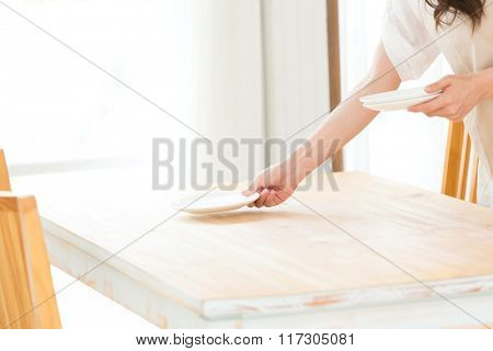 Woman holding plates and dishes in her kitchen