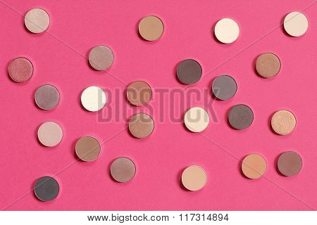 pattern of bronze eyeshadow on pink background