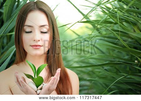 Beautiful young woman on green natural background