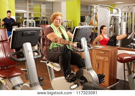 Fat woman doing workout on exercise bike in gym.