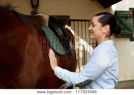 Happy woman caressing brown horse.