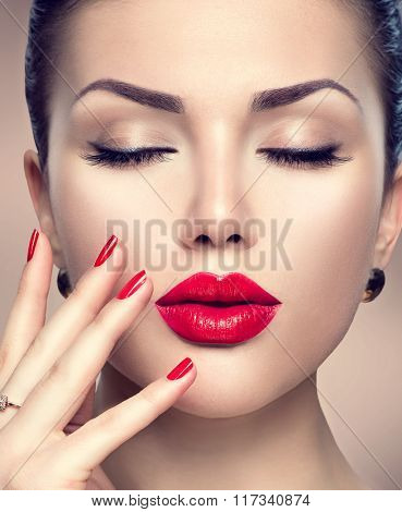 Beautiful Fashion woman model face portrait with red lipstick and red nails. Glamour girl with bright makeup. Beauty female. Perfect skin and make up. Red lips and nail polish