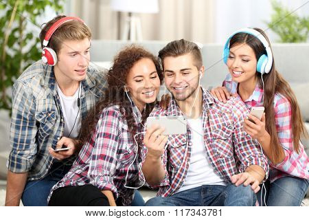 Two teenager couples listening to music and taking photo with mobile phone in living room