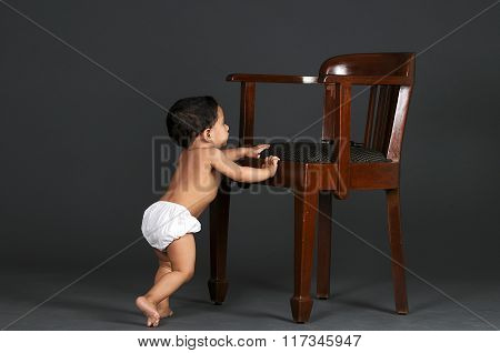 One year old boy trying to stand by holding a chair.