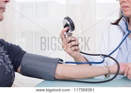 Doctor Using Sphygmomanometer And Stethoscope