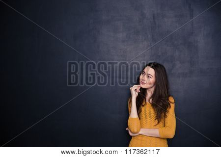 Portrait of a thoughtful woman looking away at copyspace over black background