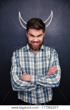 Portrait of handsome man pretending devil standing with arms crossed over chalkboard background with drawn horns