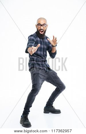Funny baldheaded young african american man with beard standing and showing karate kick