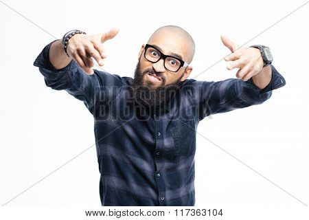 Angry aggressive african american baldheaded man with beard in glasses pointing to camera with both hands