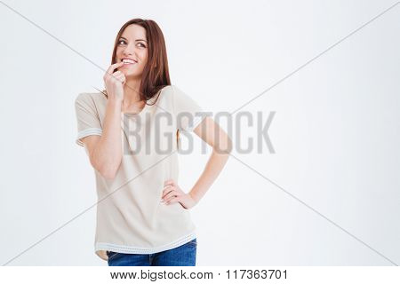 Happy charming young woman with long hair smiling and thinking over white background
