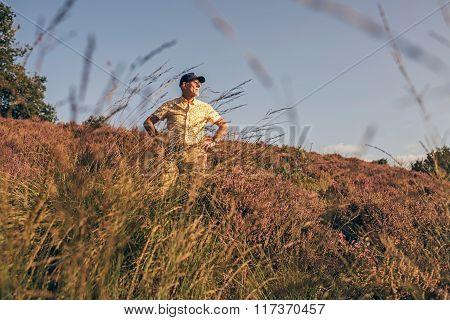 Retired Man Standing In Summer Heathland.